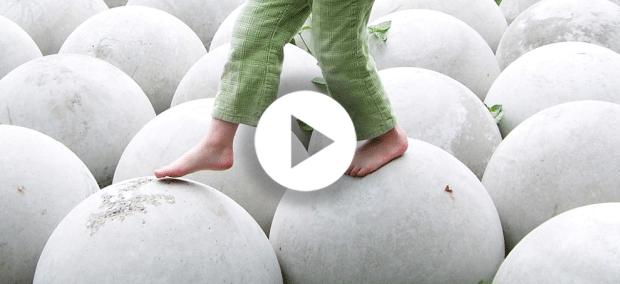 free-child-walking-in-balance-on-white-spheres